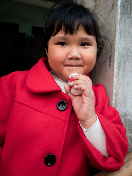 girl in red eating a candy