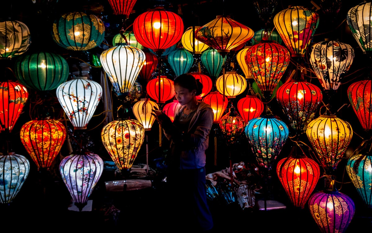 woman standing amid hoi an lanterns in the night market