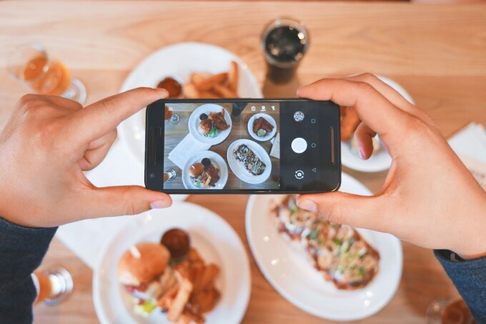 person taking a picture of a table of food