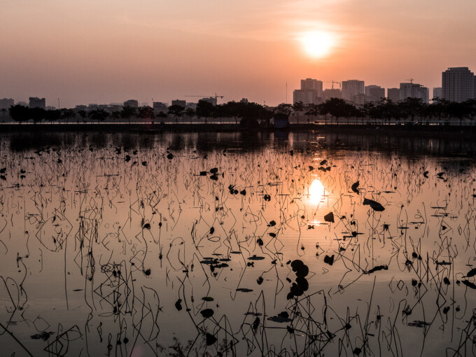 sun setting over west lake in hanoi
