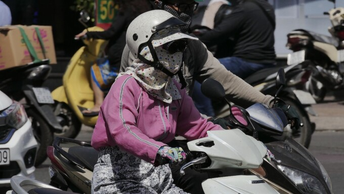 woman driving a scooter in crowded saigon