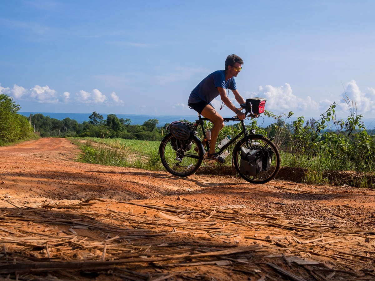 stephen cycling a red dirt road in cambodia