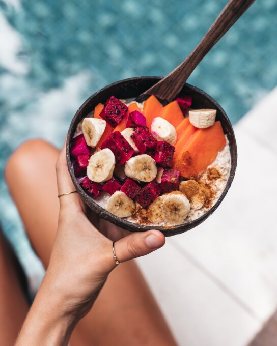 woman holding smoothie bowl by swimming pool