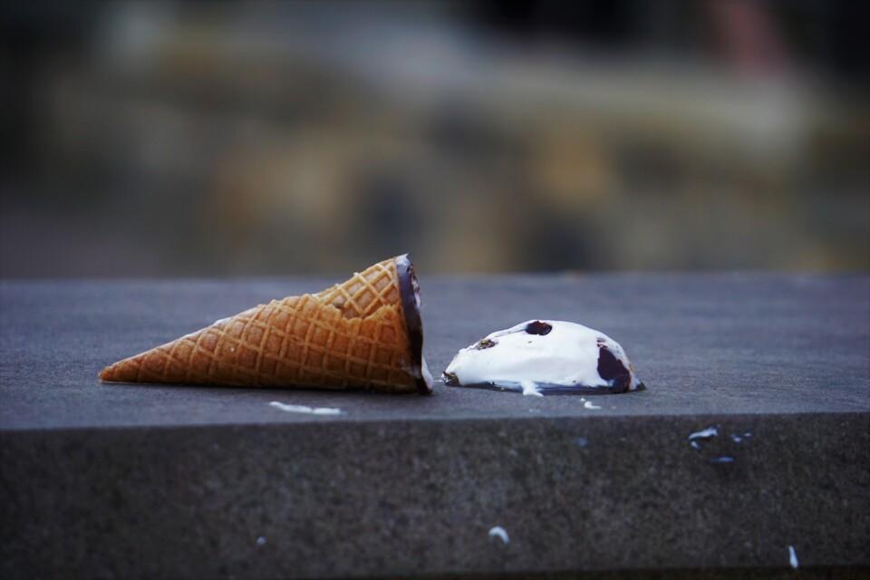ice cream cone melting on the sidewalk