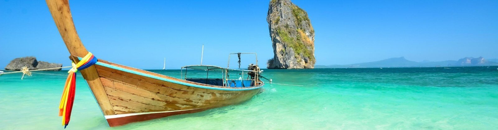 wooden boat on turquoise water in thailand
